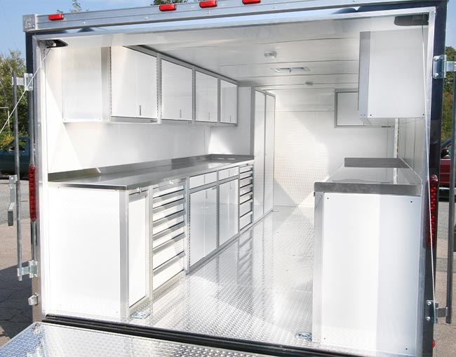 Trailer interior with white Pro II series storage cabinets on both sides